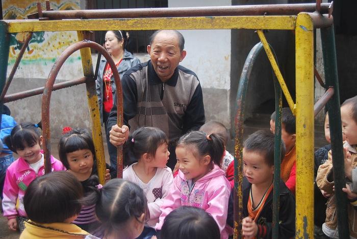李泽安与幼儿园的小朋友一起玩